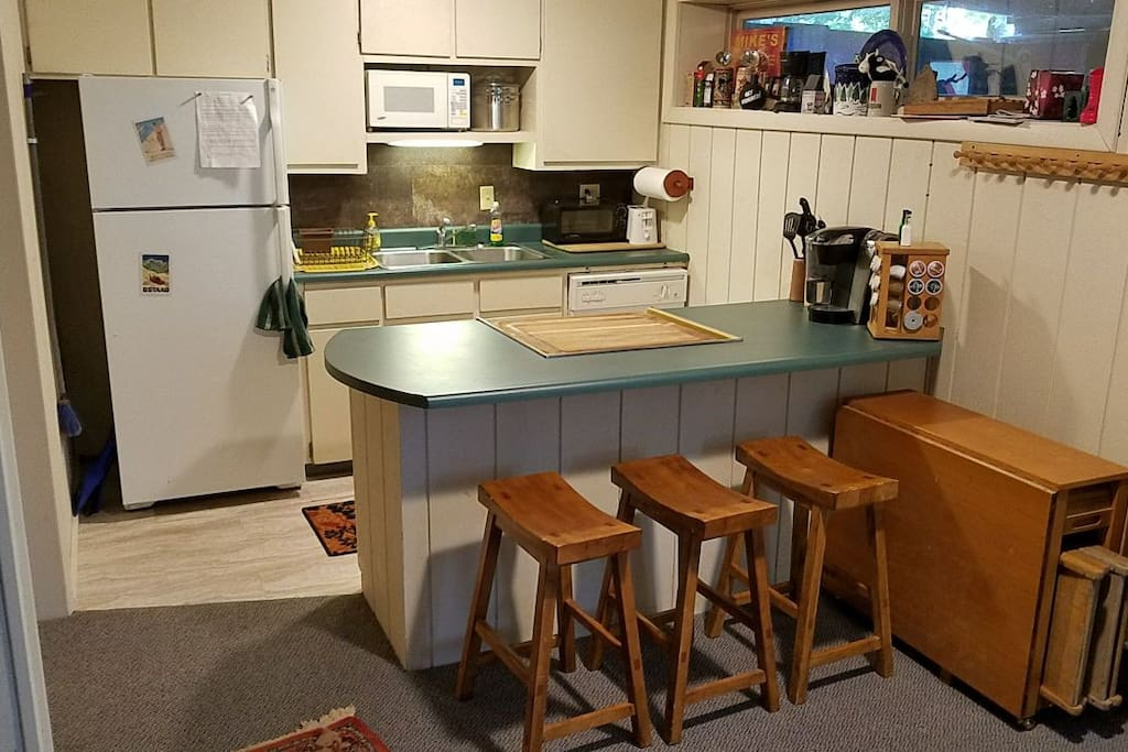 Island for eating or hanging out.  Oven is built in under the cutting board.  Wooden folding table seats 1 to 6 people.  Picture taken from living space.  Private entrance to the right.