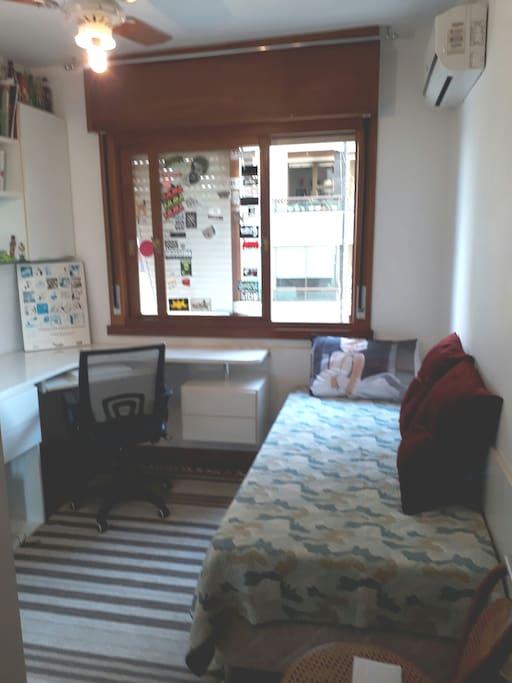 quarto disponível com bancada de trabalho, ar condicionado e cama de solteiro
