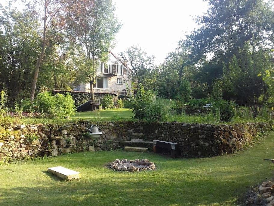 Notre maison domine un jardin de 1300m2 qui vous plongera dans un havre de paix. Vous serez en communion avec la nature, entourés d'arbres et n'entendrez que le bruissement des feuilles et le chant des oiseaux.