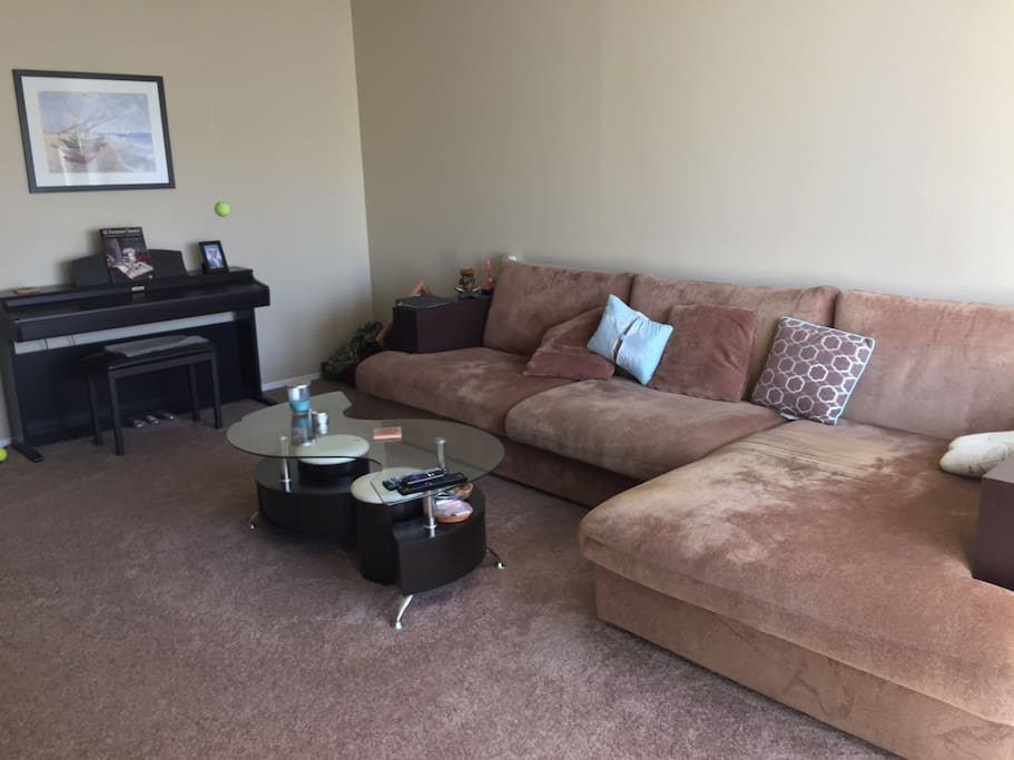 Living room. Large couch, tv, piano
