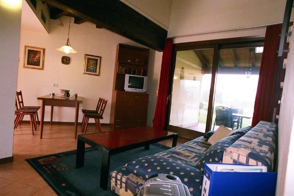 Wohnzimmer mit Esstisch, Schlafcouch und Blick auf die Terrasse