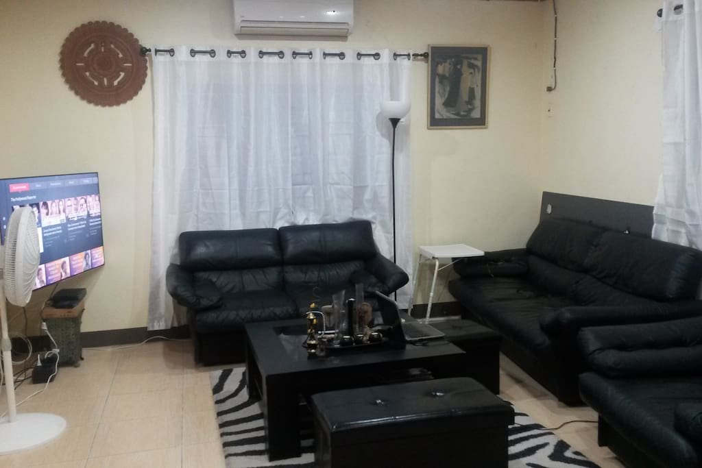 Living room with flat screen, AC, fan and large comfy sofa