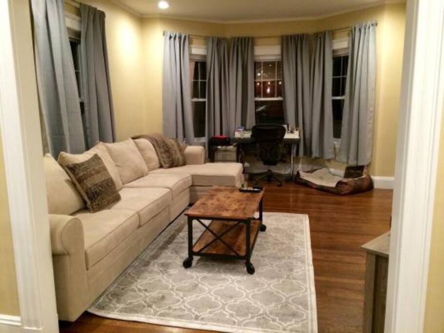 """Living Room w/ desk looking out over the park. To the right there is a 60"""" flat screen TV."""