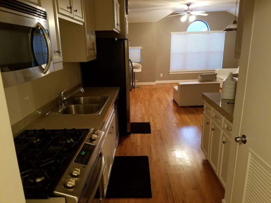 Stainless steel kitchen with microwave, gas stove and fridge