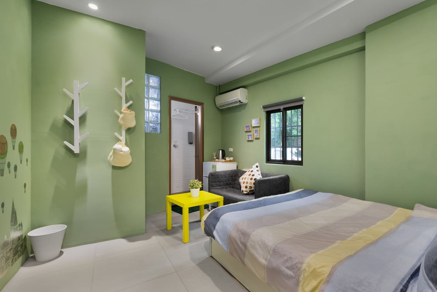 Room with double bed , private bathroom and small living room.