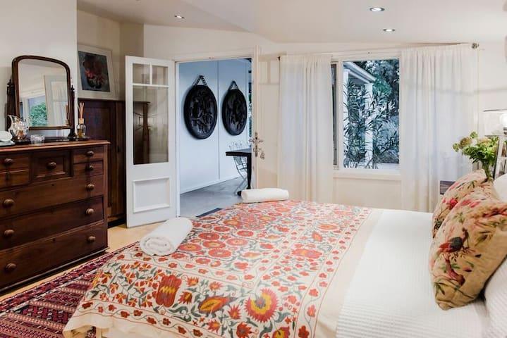 Spacious queen bedroom with private bathroom overlooking the garden oasis