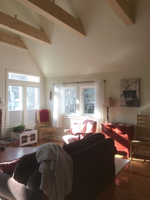 The bright, spacious living room is on the upper level and is surrounded by trees.