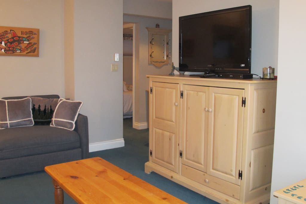 TV with playstation and comfy chair.