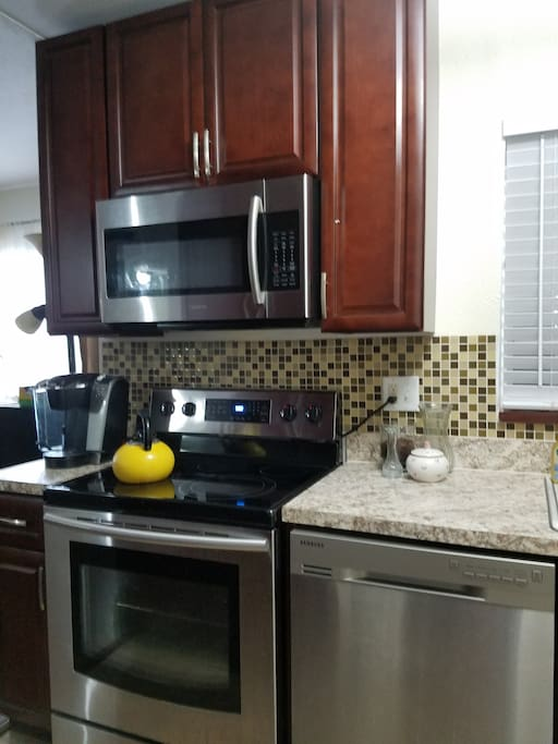 The kitchen is complete with Samsung microwave, stove/oven, dishwasher, and refrigerator, cookwares, & dinnerware.