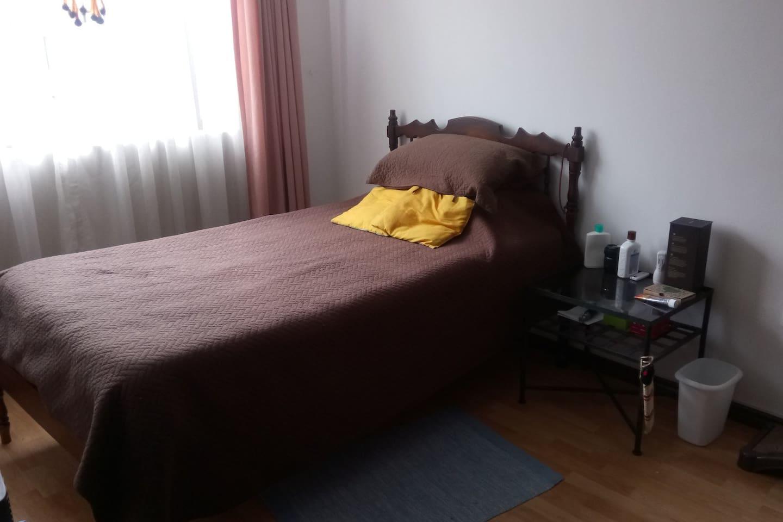La habitación tiene una cama de plaza y media, mesa de noche y closet amplio