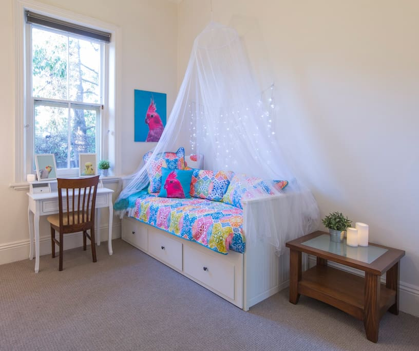Day bed as a single bed - can be extended into a king sized bed. Writing desk in room.