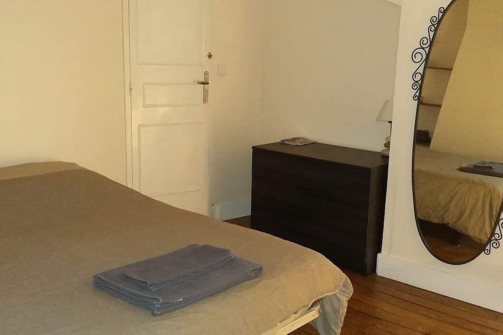 La chambre mansardée avec un velux, bureau, rangements, miroir, draps, serviette.