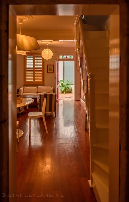 From the kitchen, the view through to the laneway via the dining and living rooms, with stairs up to the bedroom on the right.