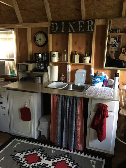 Tiny kitchen area with fridge and coffee maker.