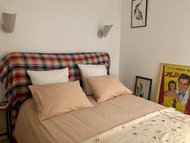 Chambre 1 avec lit double donnant sur une courette privative, avec store extérieur en bambou. Linge de lit fourni.