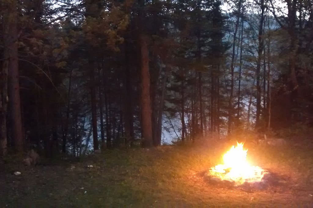 Espace de feu de camp et rivière Ouareau passant sur la propriété.