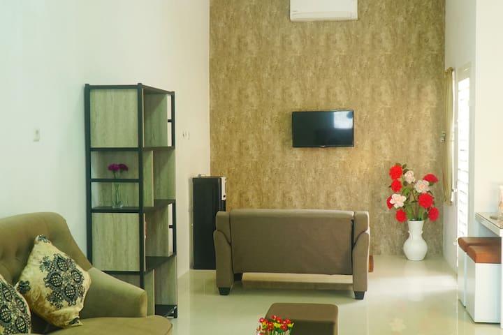 Ruang keluarga yang nyaman dilengkapi dengan sofa 2 seat, meja, televisi, AC, kipas angin, karpet, dan standing dispenser.