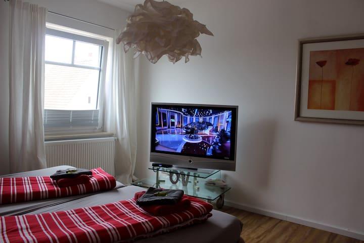 ein Doppelzimmer mit einem 2 x2m Doppelbett und großem Ferneseher