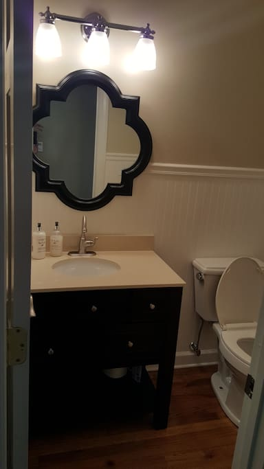 Powder room is located between the kitchen and the living room.