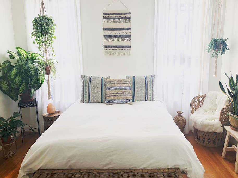 airy + bright bedroom with lots of plants all throughout