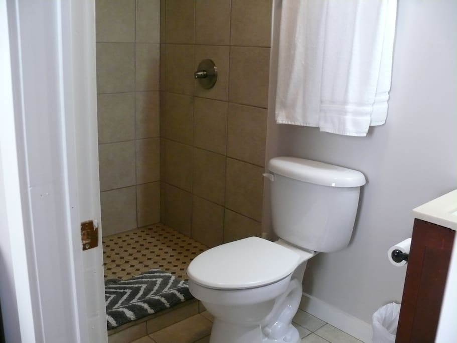 Tile bath with large step-in shower and ample white fluffy towels