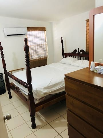 fist bedroom, equipped with ac conceal, dresser and queen size bed