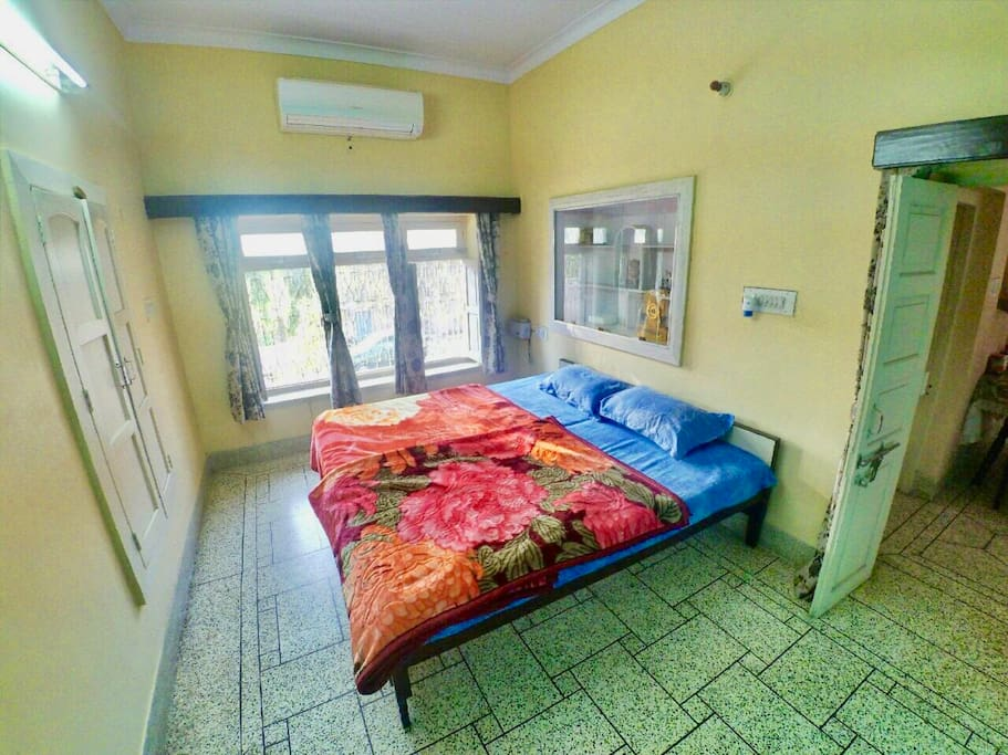 Chip (Room 2: AC):  A relaxing cream color painted room comes with AC newly fitted AC not notch O'General Air conditioner. This room sports a huge entire wall set window with a beautiful garden view. The room also has mat white colored royal wooden word.