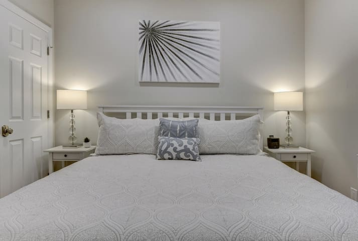 Pristinely white bedroom with a king bed, two closets, and two nightstands with storage.