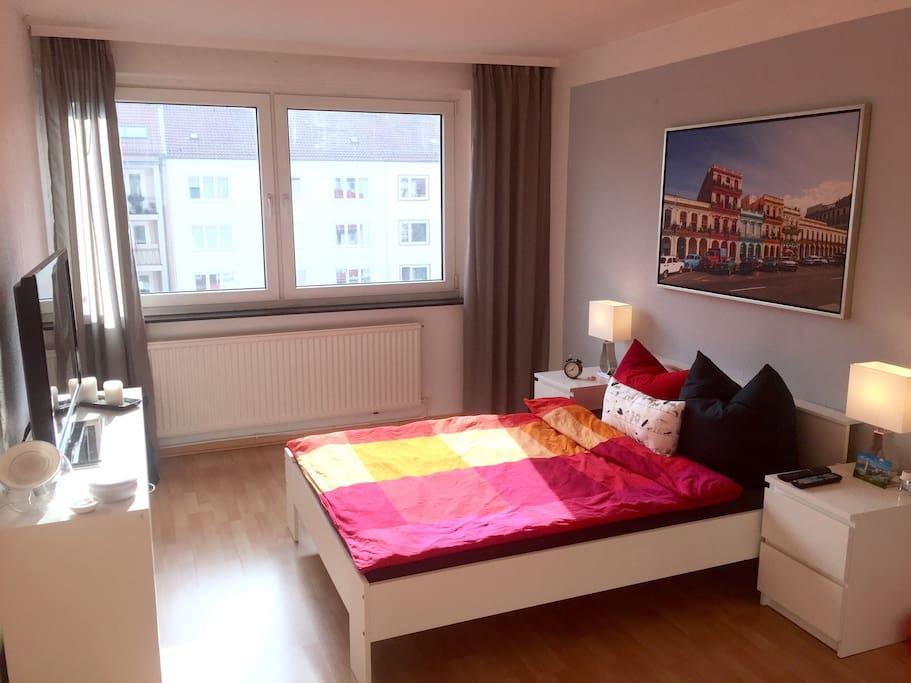 Schlafzimmer mit Fernseher und Kleiderschrank