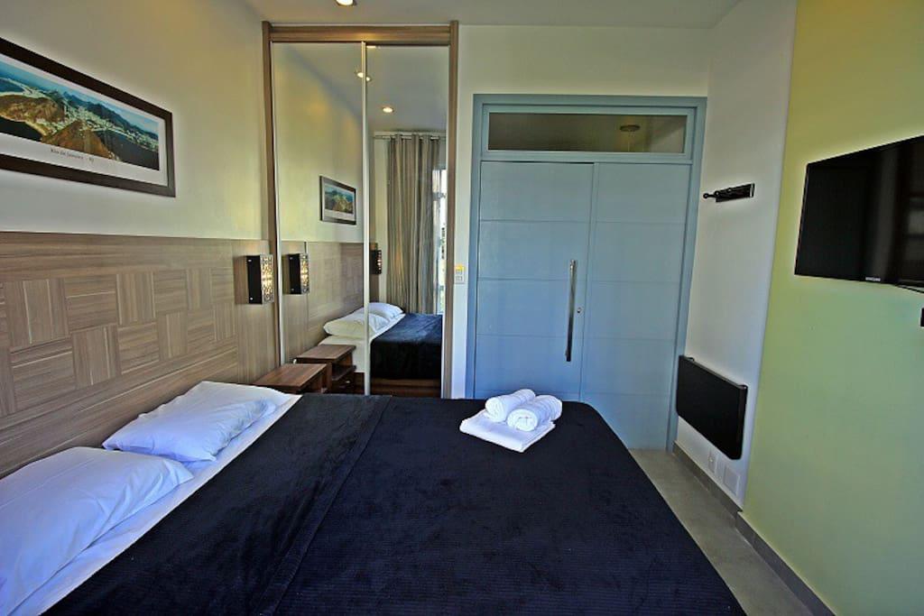 Quarto com cama de casal, asr condicionado, TV LCD e armário.