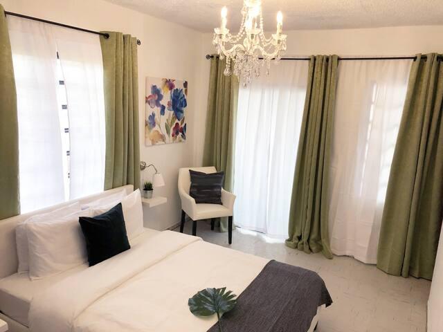 Vista del cuarto de habitacion el cual incluye toallas y ropa de cama,mesa de noche con lámpara, closet, butaca, TV con sistema ROKU, Internet y una cama Queen para 2 personas.