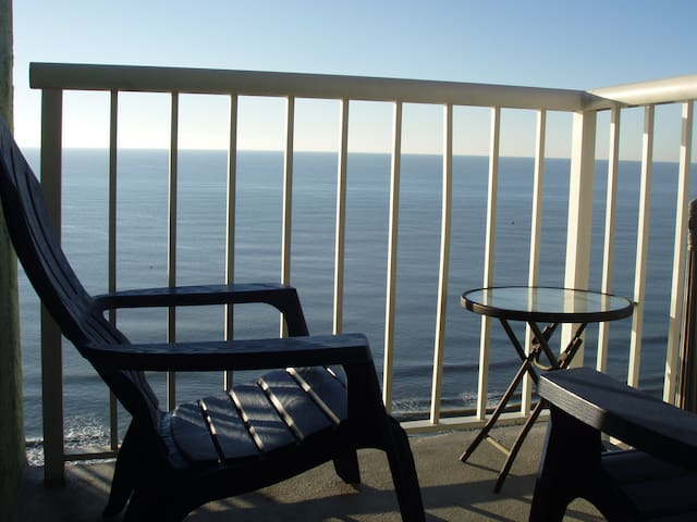 balcony with a direct oceanfront and expansive view of the ocean and coastline; since it's an end unit. Two  comfortable chairs. Breathtaking sunrises and sunsets. Bring your camera!
