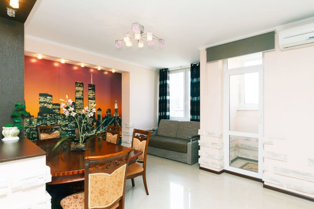 A cozy kitchen area separated by a partition with access to a glass balcony, with air conditioning above the balcony door, a dining wooden table, 4 chairs, a comfortable sofa bed can be used as an extra bed.
