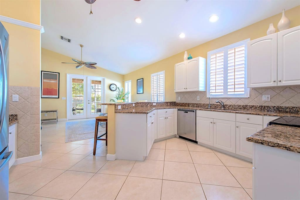 Fully equipped kitchen with large fridge, high ceilings and lots of natural light. View towards the living room.