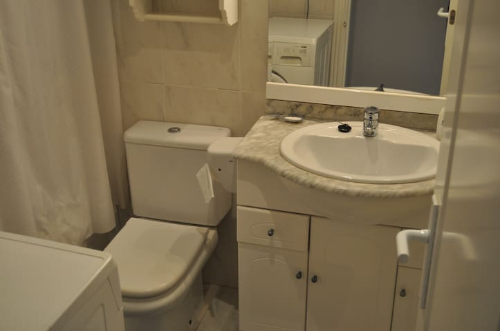 one of the two bathrooms with washing machine and bath tub