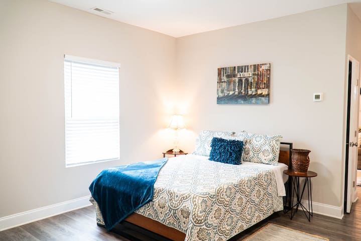 This bedroom has a comfortable queen sized bed, airy ceiling height, calming paint palette, with easy access to the kitchen, bathroom, and living room.