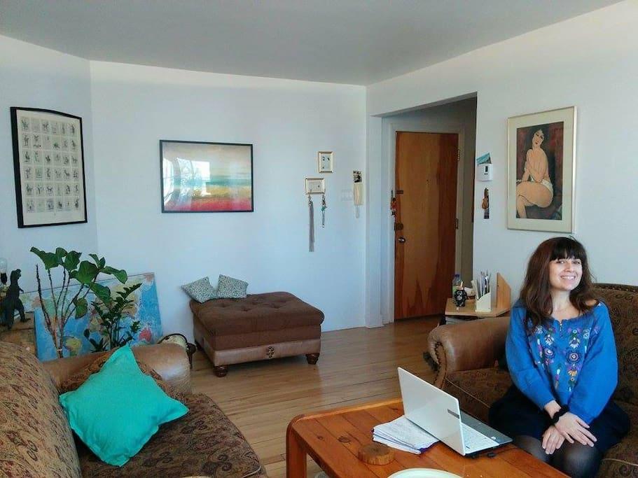 Salon lumineux sur balcon et ouvert sur corridor qui amène aux chambres, SDB et cuisine, deux confortables canapés, ma colocataire la chaleureuse Lydie