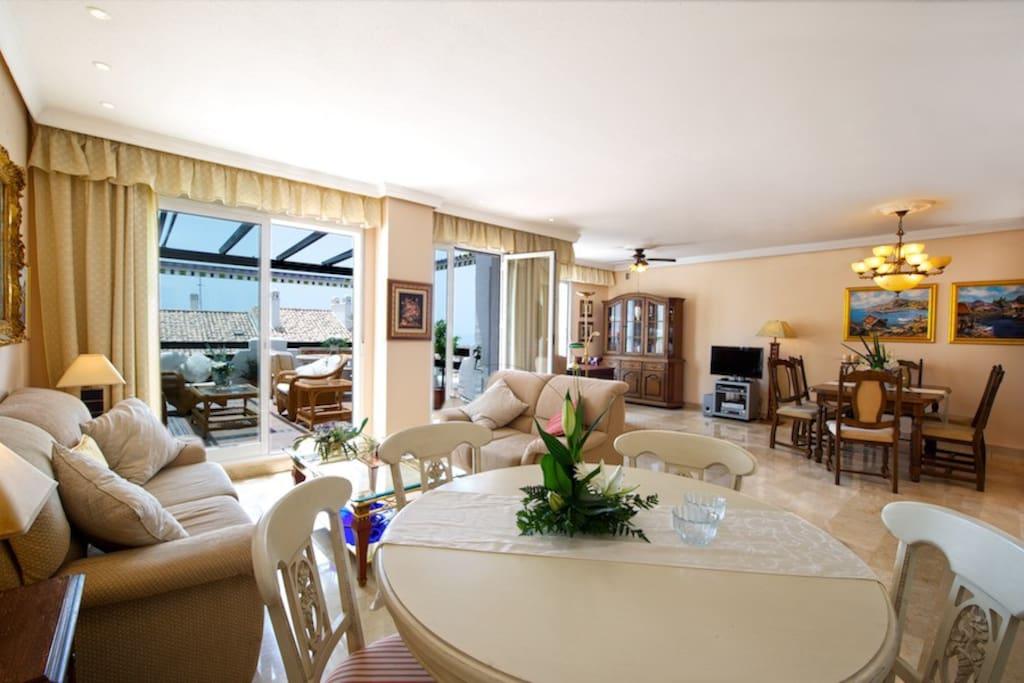 Stor stue med sofagruppe og 2 spisebord TV.