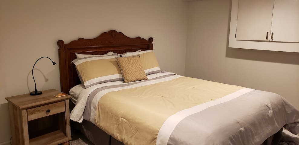 Second bedroom with queen size bed, walk in closet, extra bedding, night table and lamp.