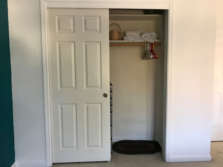 Closet with hangers, storage, and clean towels