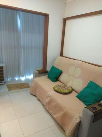 Sala com TV, sofá-cama e mini varanda