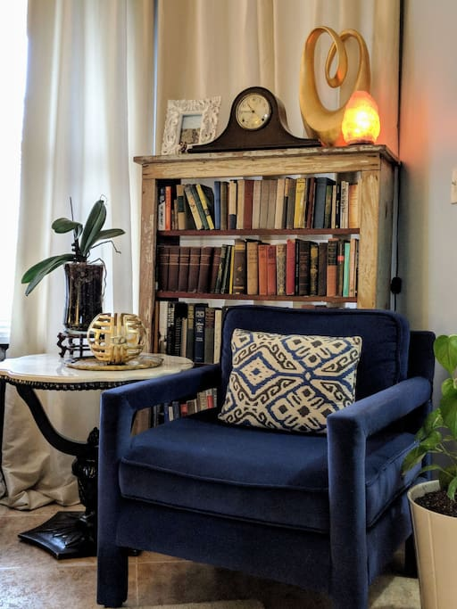 Throughout the home are unique spaces like this vignette from our vintage designer living room featuring a stunning pair of velvet Parson chairs by Milo Baughman.