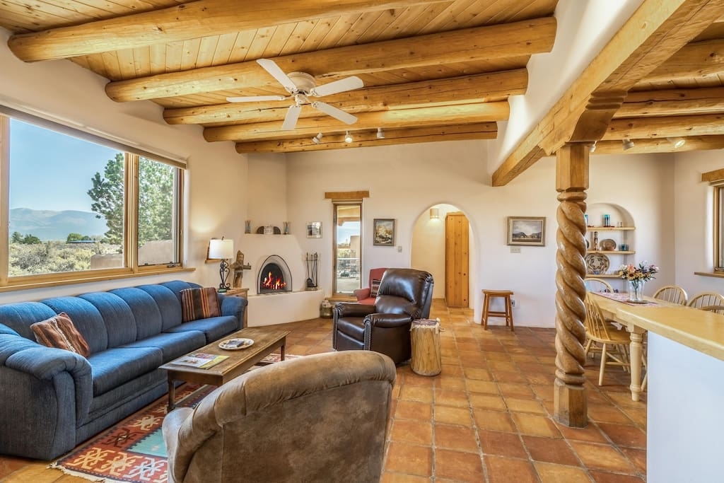 The living room is crafted with tiled floors and exposed beams and has both a classic kiva fireplace and a gas stove.