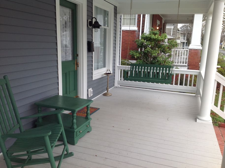 Front Porch with swing, rocking chairs and tables.