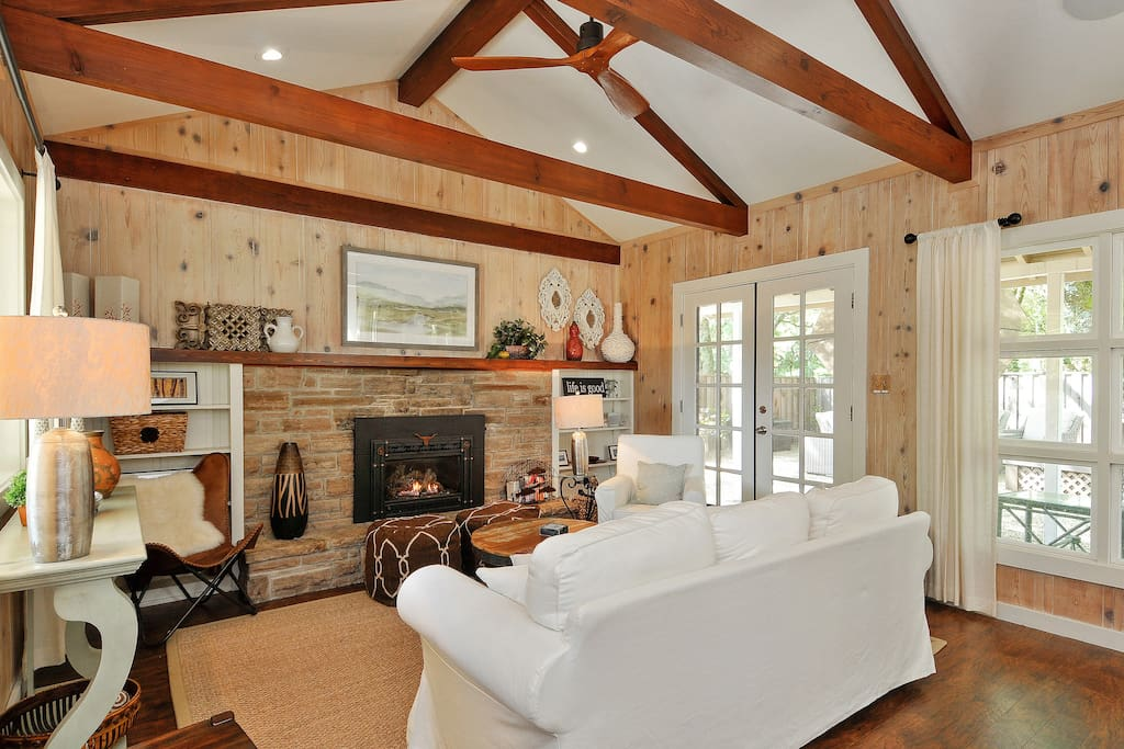 Rustic walls, a natural stone fireplace and wooden beamed ceilings in the living room creates a lodge like feeling of casual elegance.