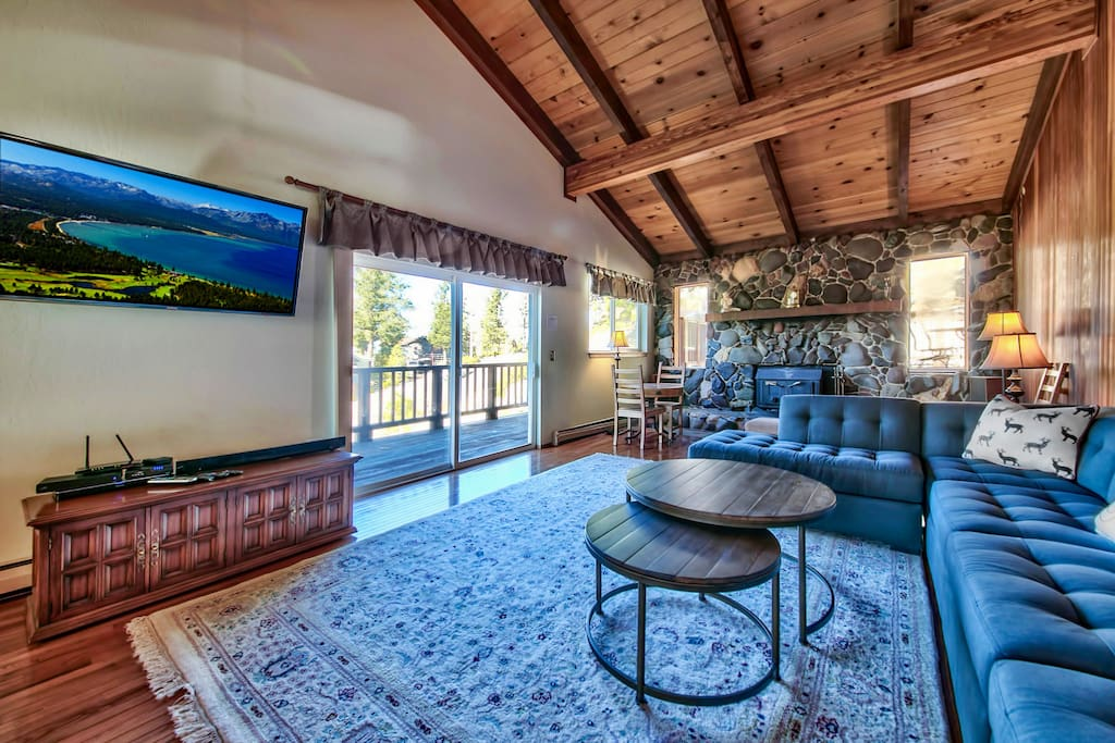 Living room with wood-burning fireplace, opens to wrap-around deck and views, now with a brand new larger HDTV!