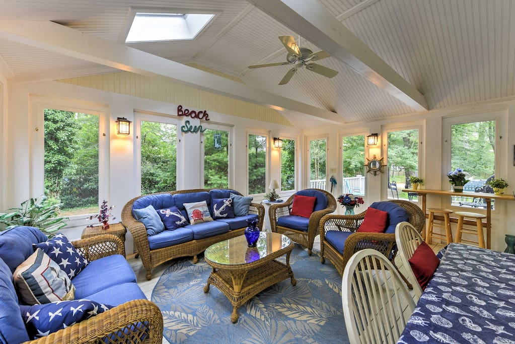 The beautiful sunroom provides fabulous views of the surrounding greenery, along with nautical decor.