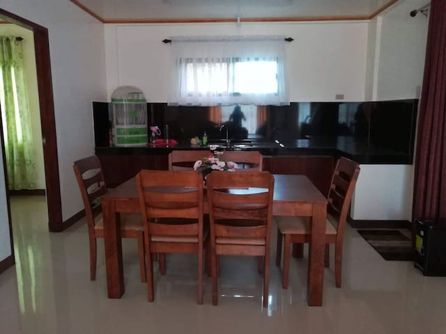 This is the dining area. Electric stove and rice cooker is available so you may cook and dine with your group. The open room on the left is the queen bedroom.