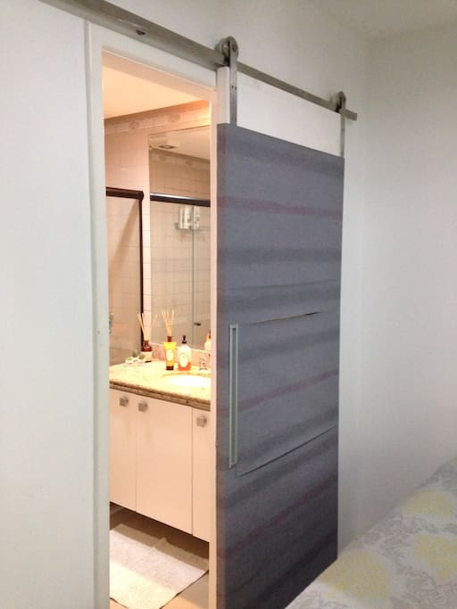 Banheiro privativo com chuveiro e bancada espaçosa.