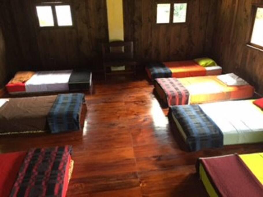 Una habitación con 8 camas imperial, con ropa de cama